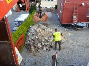 """Renova, Her grabber vi opp, før bortkjøring av jord, stein og betong med en av våre kranbiler. Vi har ofte med en hjelpemann til å krafse og rake, slik at det skal se """"strøkent"""" ut etter oss. (De fleste andre firmaer har bare én mann på kranbilen og gjør det litt mer røft, siden de ikke har tid til den siste finpussen....)"""