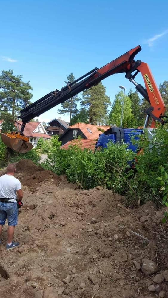 Bortkjøring av jord og stein. Her benytter vi kranbil med grabb over en hekk